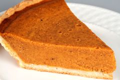 Pumpkin Pie - closeup. A slice of pumpkin pie served on a plate. This image can easily be isolated for insertion anywhere in your design royalty free stock photo