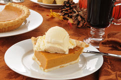 Pumpkin pie and mulled wine. A slice of pumpkin pie ala mode with hot spice wine royalty free stock photos