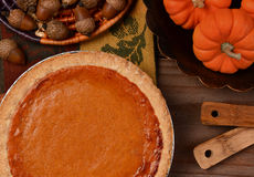 Pumpkin Pie. Overhead view of a fresh baked pumpkin pie ready for Thanksgiving. The pie is surrounded by autumn accessories including acorns, and mini pumpkins Stock Image
