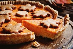 Pumpkin pie piece cut out of whole pumpkin pie. Thanksgiving day food Stock Image