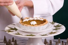 Pumpkin Pie Piping. Close up action shot of a uniformed Pastry Chef piping whipped cream shell border on a small maple pumpkin pie Stock Photos