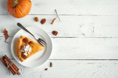 Pumpkin Pie. With whipped cream, pecan nut and cinnamon on white wooden background, top view, copy space. Homemade autumn pastry for Thanksgiving - piece of stock photo
