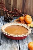 Pumpkin Pie in Red Pie Plate. Homemade pumpkin pie in red ceramic pie plate over a rustic wooden background. Extreme shallow depth of field with selective focus stock photography