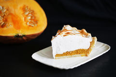 Pumpkin pie slice with meringue and squash on black, isolated Royalty Free Stock Images