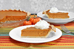 Pumpkin pie slice with whole pie in background. Royalty Free Stock Photos