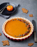 Pumpkin pie, tart made for Thanksgiving day in a baking dish Grey stone background. Royalty Free Stock Photo