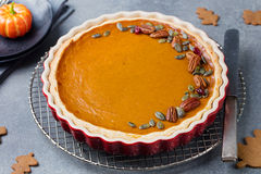 Pumpkin pie, tart made for Thanksgiving day in a baking dish Grey stone background. Royalty Free Stock Image