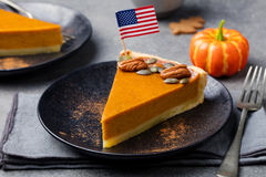 Pumpkin pie, tart made for Thanksgiving day on a black plate with American flag on top. royalty free stock images