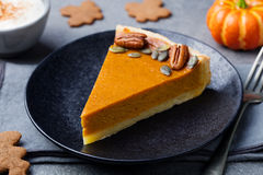 Pumpkin pie, tart made for Thanksgiving day on a black plate. Grey stone background Stock Photos