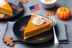 Pumpkin pie, tart made for Thanksgiving day with whipped cream with American flag on top. Stock Image