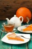 Pumpkin pie, tea in glass cup, white teapot and fresh pumpkin on Stock Photo