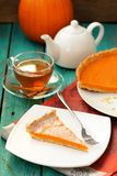 Pumpkin pie, tea in glass cup, white teapot and fresh pumpkin on Stock Photography