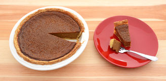Pumpkin pie for Thanksgiving with a slice on a plate Royalty Free Stock Image