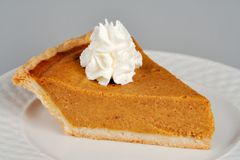 Pumpkin Pie with Whipped Cream. A slice of pumpkin pie topped with a dapple of whipped cream. This image can easily be isolated for insertion anywhere in your royalty free stock photos