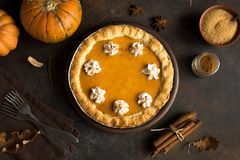 Pumpkin Pie. With whipped cream and cinnamon on rustic background, top view. Homemade pastry for Thanksgiving traditional stock photos