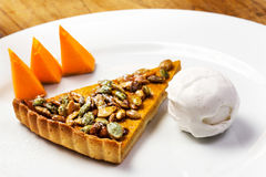 Pumpkin Pie with whipped cream and pumpkin pieces on white plate Royalty Free Stock Photos