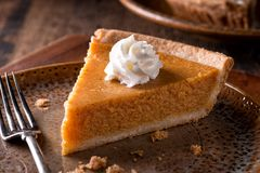 Pumpkin Pie with Whipped Cream. A slice of delicious home made pumpkin pie with whipped cream on a rustic table top Royalty Free Stock Photo