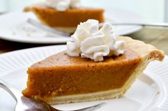 Pumpkin pie on a white plate stock image