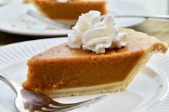 Pumpkin pie on a white plate. Pumpkin pie with whipped cream on a white plate royalty free stock images