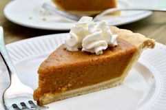 Pumpkin pie on a white plate. Pumpkin pie with whipped cream on a white plate stock photography