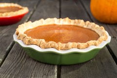 Pumpkin Pies. Freshly baked pumpkin pies cooling on rough wood boards. Green and red ceramic pie plates. Fresh pumpkin in the background royalty free stock image