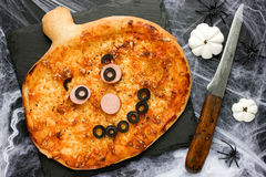 Pumpkin pizza with cheese, olive and sausage. Creative food idea stock photography