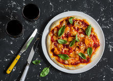 Pumpkin pizza and two glasses of red wine on dark background Royalty Free Stock Image