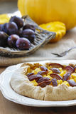 Pumpkin, plum and apricot galette on wooden table Royalty Free Stock Photos