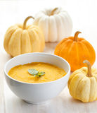 Pumpkin porridge and pumpkins on white wooden table Royalty Free Stock Photography
