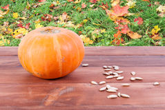 Pumpkin and pumpkin seeds on a wooden table Royalty Free Stock Photography