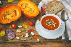 Pumpkin soup puree in white bowl on wooden table. Pumpkin puree soup in white bowl on wooden table, seeds, onions, leaves, rustic style, autumn composition Royalty Free Stock Photos