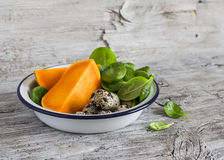 Pumpkin, quail eggs, spinach in the enameled bowl - raw ingredients for cooking, on a light rustic wood table. Stock Photos