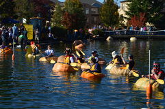 Pumpkin races. People racing around a pond in huge carved out pumpkins wearing all kinds of costumes during the Tualatin Pumpkin race at Halloween time royalty free stock photo