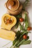 Pumpkin ragout contrast lightning vertical. Raw Pumpkin on cutting board with clay pot Stock Image