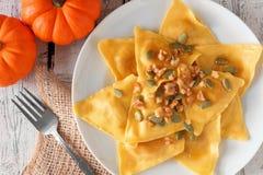 Pumpkin ravioli pasta, close up on rustic white wood. Pumpkin filled ravioli pasta with nuts, pumpkin seeds and olive oil, close up on a rustic white wood Stock Photos
