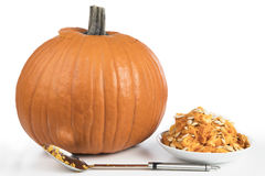 Pumpkin Ready for Carving. Recently cleaned pumpkin with seeds in bowl and large spoon, ready for carving royalty free stock image