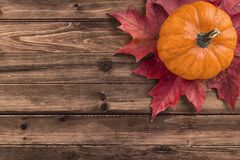 Pumpkin with red maple leafs disposed on wooden table. stock photography
