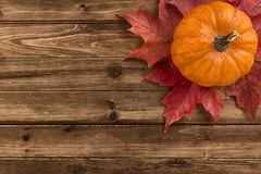 Pumpkin with red maple leafs disposed on wooden table. royalty free stock photo