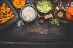 Pumpkin risotto cooking ingredients on dark rustic kitchen table with bowls, spoon and pan, top view, border. Vegetarian food royalty free stock image