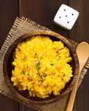 Pumpkin Risotto. Prepared with pumpkin puree and sprinkled with fresh thyme leaves served in wooden bowl, photographed overhead with natural light (Selective Stock Photo