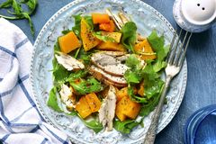 Pumpkin salad with chicken and arugula.Top view. Pumpkin salad with chicken and arugula on a vintage plate over dark blue slate,stone or concrete background.Top royalty free stock image