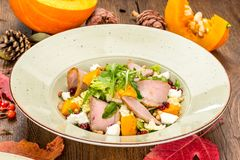 Pumpkin salad with meat shot on a wooden plank background. Pumpkin salad with meat shot on a wooden background from boards close up stock photography