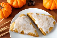 Pumpkin scones with frosting, on plate with wood background Royalty Free Stock Photos