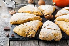 Pumpkin scones with walnuts and chocolate for breakfast on a dark wooden background. Royalty Free Stock Images