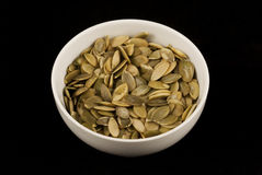 Pumpkin seed bowl. Close up of bowl full of pumpkin seeds stock images