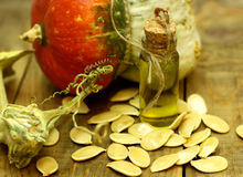 Pumpkin seed oil in vintage bottle on a wooden table. Organic farmers food.