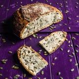 Pumpkin seed sourdough bread. On a purple wooden board stock photos
