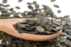 Pumpkin seed in a wooden spoon and forming a background Royalty Free Stock Images