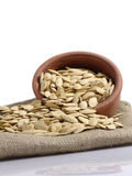 Pumpkin seeds. Fresh and natural on terracotta and linen. isolated white backgrounds Stock Photography