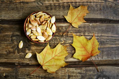 Pumpkin seeds and autumn maple leaves Royalty Free Stock Images